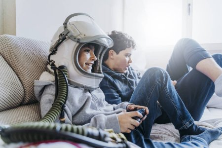 Photo for Two kids lying on couch and playing with a video game console at home - Royalty Free Image