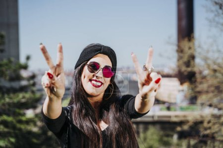 Photo for Beautiful woman making peace sign in the street. - Royalty Free Image