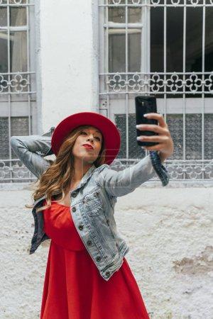 Photo pour Femme portant une robe rouge sur le téléphone intelligent dans la rue - image libre de droit