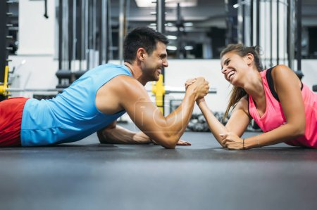 Photo for Two athletes doing arm wrestling challenge while lying on floor of gym - Royalty Free Image