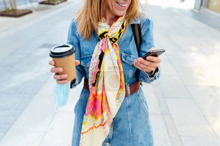 Photo for Woman with coffee and mobile phone on the street. - Royalty Free Image