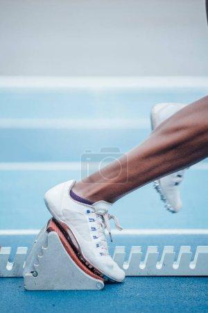 Photo pour Femme de sport afro méconnaissable en tenue de sport commençant la course à partir de la position de départ accroupie sur les blocs de départ - image libre de droit
