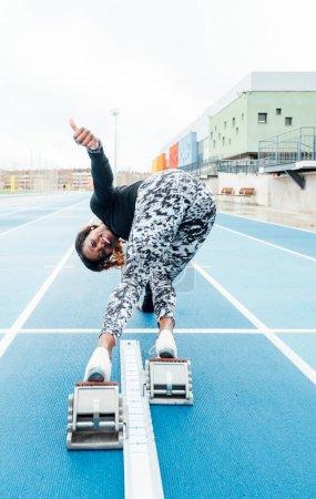 Photo pour Vue arrière d'une jeune sportive agitant la caméra avant de décoller - image libre de droit
