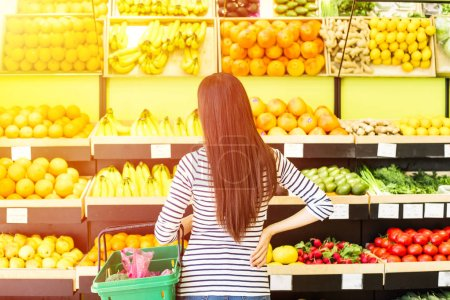 Rear view of longhaired brunette woman with basket trying to choose fruits in grocery
