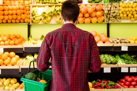 Rear view of young caucasian man in checkered shirt in grocery store