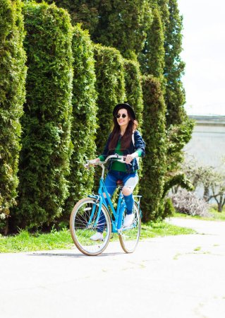 young casual girl riding on bike on green trees background