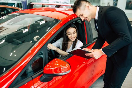 woman sitting in new car in dealership discussing documents with male consultant