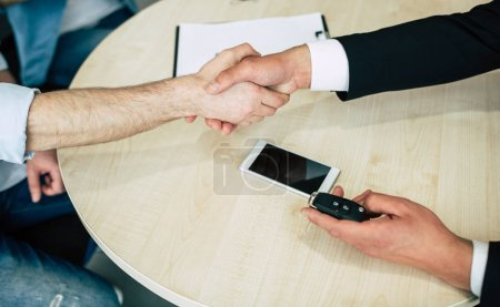 Handshake of seller and buyer and transfer of keys in dealership