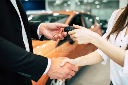 woman  receiving key of new car from salesman in dealership, close up of hands
