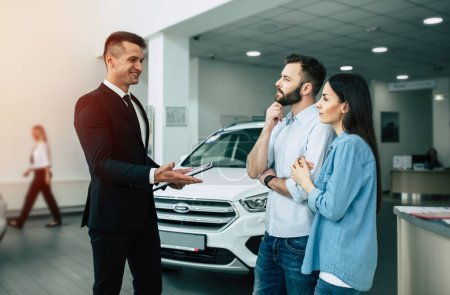 car salesman in dealership telling young customers about stock in store