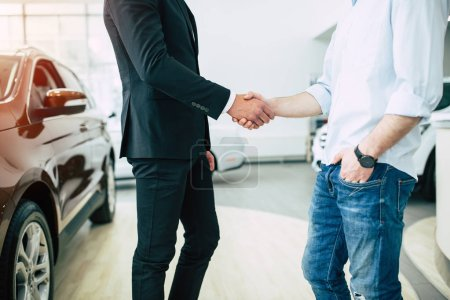 Male consultant and customer shake hands standing in dealership on cars background, crop