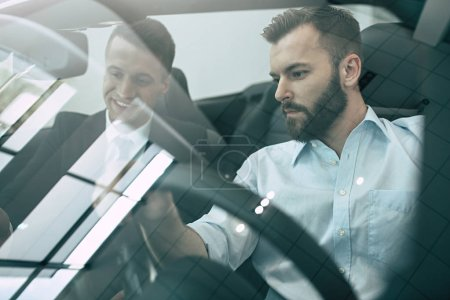 two businessmen sitting in new cabriolet at dealership