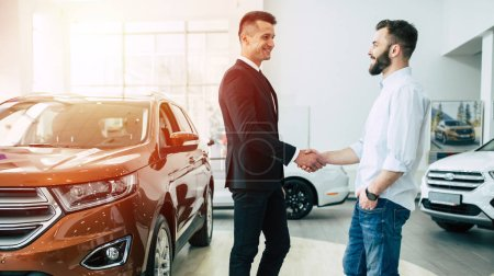 Male consultant and customer shake hands standing in dealership on cars background