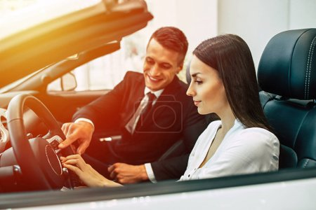 Functionality of car salon. Smiling consultant of dealership showing design features of car for beautiful female client