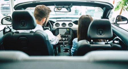 happy couple sitting in new car in dealership, rear view, choosing car concept