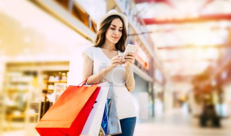 Photo pour Jeune femme avec des sacs à provisions en utilisant le téléphone au centre commercial - image libre de droit