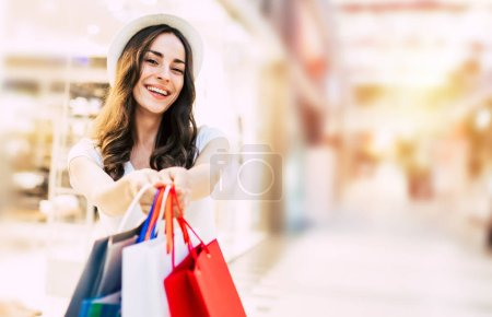 Photo for Happy young woman with shopping bags at mall giving it to camera - Royalty Free Image