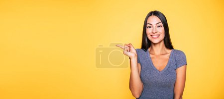 Photo for Portrait of smiling brunette gesturing with finger on yellow background - Royalty Free Image