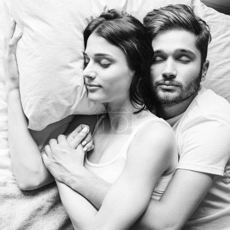 Photo pour Jeune couple hétérosexuel câlins sur le lit - image libre de droit