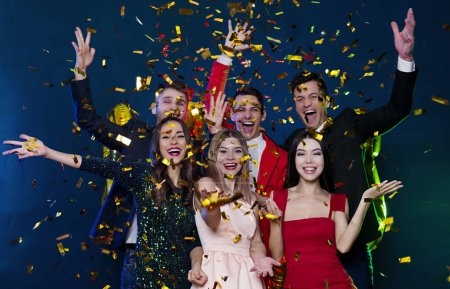 Photo for Group of happy friends celebrating new year with golden confetti - Royalty Free Image