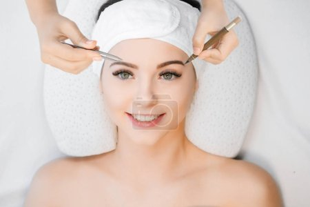 Photo pour Vue de la femme à la procédure pour la forme des sourcils formant dans le salon de beauté - image libre de droit