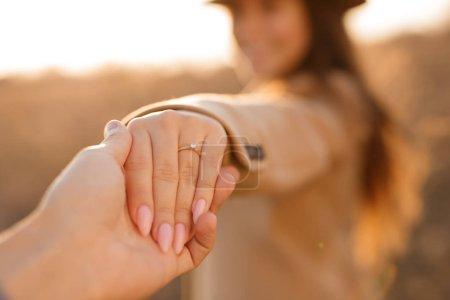 Photo pour Main masculine tenant la main de sa petite amie main avec anneau sur doigt - image libre de droit