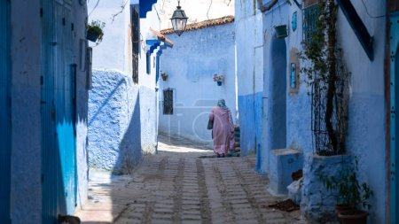Chefchaouen , Morocco - April 2018: Unidentified woman walking in blue medina of Chefchaouen city in Morocco, North Africa