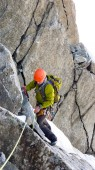 male mountain climber traverses a tricky rock chimney on his way to a high alpine summit