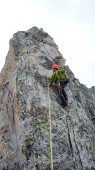 male mountain guide lead climbing on an exposed granite ridge in the Alps