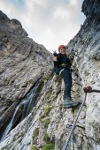 young attractive female mountain climber on a difficult Via Ferrata in the Dolomites in Alta Badia in the South Tyrol in Italy making a peace sign and smiling