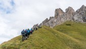 A large group of climbers and two mountain guides hiking towards the start of a climb in the Dolomites of Alta Badia in northern Italy