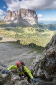 young attractive female mountain climber in the Dolomites of italy with a great view of the Langkofel and Passo Sella