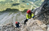 two young attractive female mountain climber in the Dolomites of italy with a great panorama view of the Langkofel and Passo Sella
