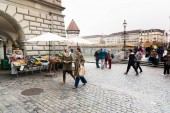 Lucerne, LU / Switzerland - November 9, 2018: many busy pedestrians and passersby and people crossing a bridge and a town square with a fruit and vegetable market stall during their busy daily routine life
