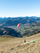 Einsiedeln, SZ / Switzerland - November 25, 2018: man with paraglider preparing for take off from a high mountain peak during an instructional course with other students already in the air and flying