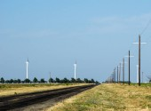 country road in the empty Texas prairie with an endless expanse of blue sky and power lines running straight to the horizon and wind turbines in the distance