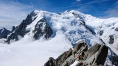 mountain guide and a male client on a rock and snow ridge heading towards a high summit in the French Alps near Chamonix