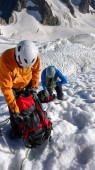 mountain climbers take a break high up on a glacier in the French Alps on their way to the Barre des Ecrins mountain peak
