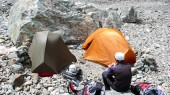 mountain climber sitting and resting at a high alpine base camp in the Barre des Ecrins National Park
