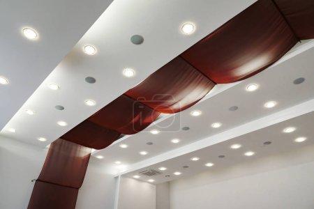 Photo pour Moderne en couches de plafond avec éclairage intégré et tissu rouge. - image libre de droit