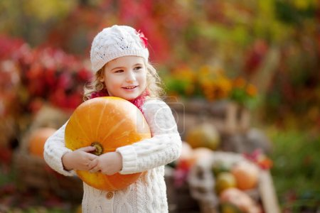 Photo for Cute little girl playing with pumpkins in autumn park. Autumn activities for children. Halloween and Thanksgiving time fun for family. - Royalty Free Image