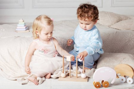 Photo for Small children playing together with a wooden toy sorter.  Little boy and girl with natural toys. - Royalty Free Image
