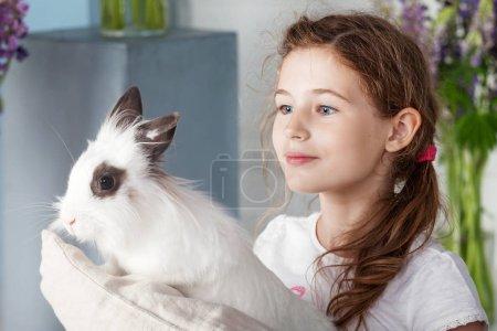 Petite fille jouant avec un vrai lapin. Lapin enfant et blanc sur E