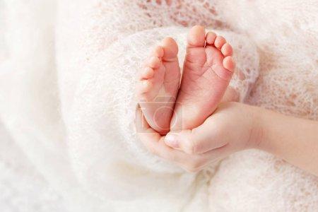 Photo pour Pieds nouveau-nés dans les mains de la mère, en forme de coeur charmant. Mère tenant les jambes de l'enfant dans les mains. Image rapprochée. Concept de famille heureuse . - image libre de droit