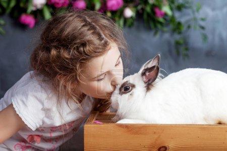 Photo pour Petite fille jouant avec un vrai lapin. Enfant et lapin blanc à Pâques sur fond de fleur. Enfant baiser animal de compagnie. Amusement et amitié pour les animaux et les enfants . - image libre de droit