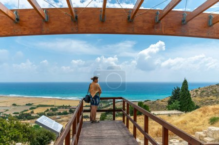 Photo for Back view of young woman standing on the bridge with ocean view - Royalty Free Image