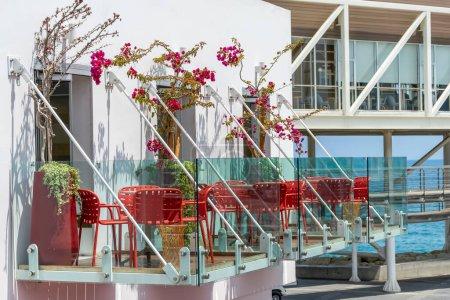 Photo pour Balcon en verre avec fleurs fleuries, tables rouges et chaises à l'hôtel - image libre de droit