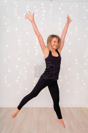 Photo pour Heureuse femme blonde sportive a sauté, sauter pour la joie de la victoire - image libre de droit