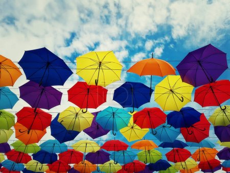Photo for Colorful umbrellas hanging above a city street isolated on blue sky background. Bright urban decoration. - Royalty Free Image