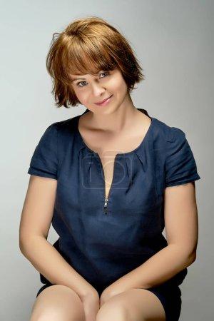 Photo pour Portrait de jeune belle femme aux cheveux roux en robe bleu marine sur fond gris - image libre de droit